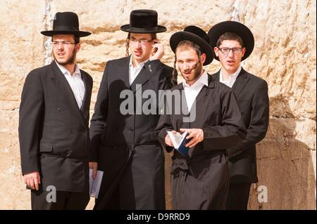 Israel Jerusalem Old City 4 Ultra Orthodox Jews standing by Wailing Western Wall Ha Kotel Plaza holding prayer books - Stock Photo