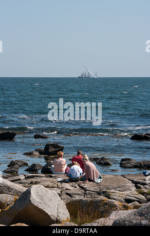 Family sitting on the rocks by the sea. - Stock Photo