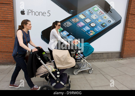 Two mothers pushing their baby's buggies, walk past a large poster for the iPhone 5 on the wall of a 'Carphone Warehouse' - Stock Photo