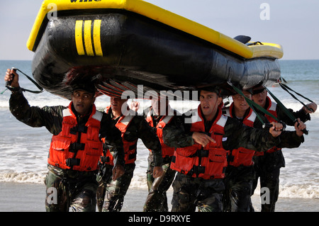 Navy SEAL candidates carry a raft during surf passage exercises on the first phase of training at Naval Amphibious - Stock Photo