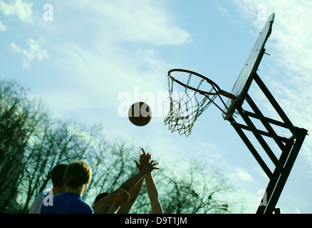People playing basketball outdoors - Stock Photo