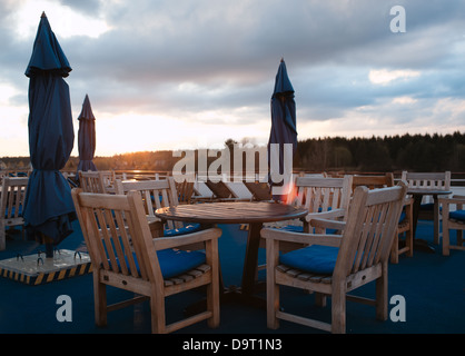 Tables in outdoor bar on stern of cruise liner - Stock Photo