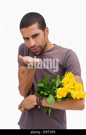 Handsome man blowing a kiss and holding roses - Stock Photo