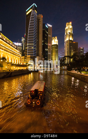 the Cavenagh Bridge, a boat on the Singapore River, the Fullerton Hotel and Central Business District at night, - Stock Photo