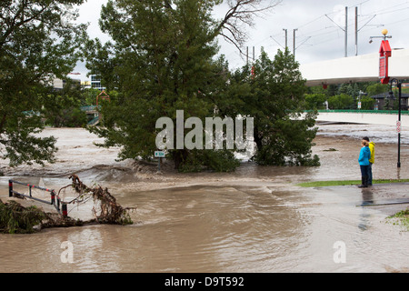 Woman and man watching the Bow River breach the bank and flood the pedestrian path in downtown Calgary - Stock Photo