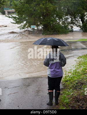 Woman holding umbrella watching the Bow River breach the bank and flood the pedestrian path in downtown Calgary - Stock Photo