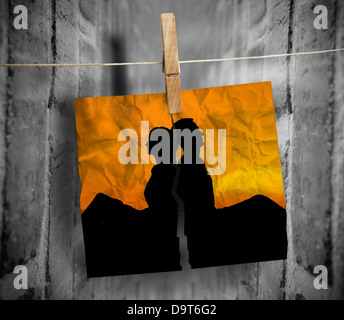 Torn photo of couple hung with a peg on a line - Stock Photo