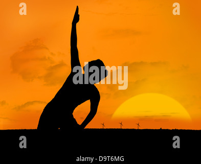 Silhouette of woman doing yoga under sunset - Stock Photo