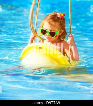 Closeup portrait of cute baby girl swinging on water attractions in aquapark, luxury entertainment on summer resort - Stock Photo