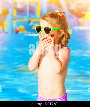 Closeup on sweet baby girl having fun in swimming pool, adorable child with red heart paint on cheek wearing cute - Stock Photo