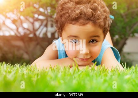 Closeup portrait of cute arabic little boy lying down on green grass field, resting outdoors on backyard, summer - Stock Photo