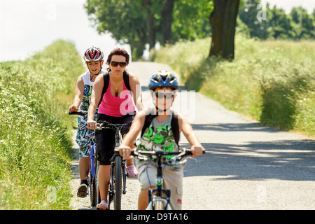Mother with two sons riding bike on bicycle trip, focus to mother - Stock Photo