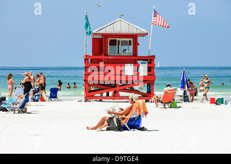 The red lifeguard tower watches over the people on Siesta Key beach FL - Stock Photo