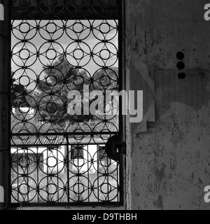 Vintage metal door with circles pattern and peeling wall of an abandoned house. - Stock Photo