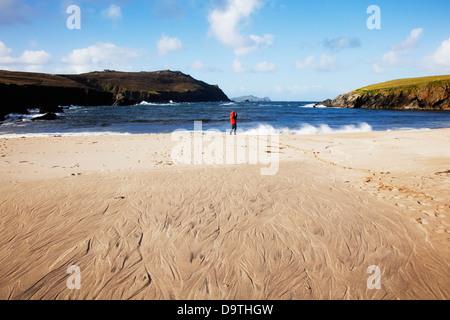 A woman standing on clogher beach in dingle;County kerry ireland - Stock Photo