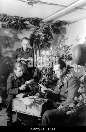 The soldiers of the German Wehrmacht read letters in a bunker on the Eastern Front on Christmas 1944. The Nazi Propaganda! - Stock Photo