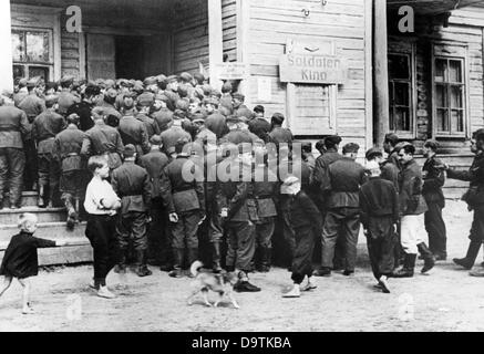 Soldiers queue in front of a cineman on the Eastern Front, published 29 July 1942. The Nazi Propaganda! on the back - Stock Photo