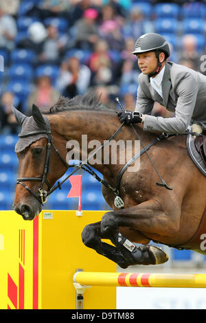 Aachen, Germany. 26th June 2013. German show jumper Marco Kutscher jumps over a hurdle on his horse Cash von Europa - Stock Photo