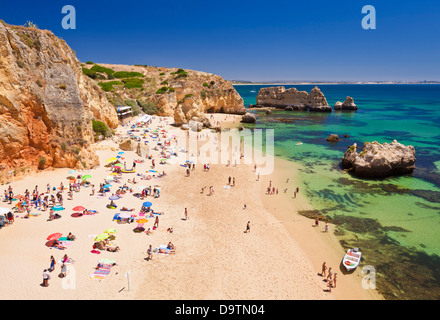 Travel Holidaymakers sunbathing on Praia da Dona Ana sandy beach near the resort of Lagos Algarve Portugal EU Europe - Stock Photo