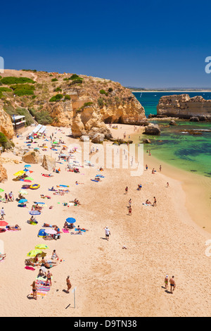 Holidaymakers sunbathing on Praia da Dona Ana Lagos Algarve Portugal EU Europe - Stock Photo