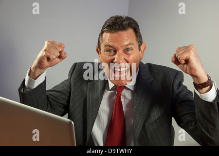Portrait business man at a desk looking to camera, cheering with clenched fists, sitting in front of a laptop. - Stock Photo