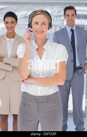 Cheerful woman with headset standing in front of business people - Stock Photo