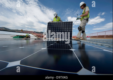 Construction workers install photovoltaic solar electric panels on the roof of the National Renewable Energy Laboratory - Stock Photo