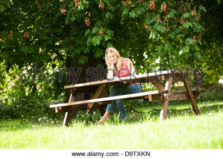 A young woman sitting on a garden bench reading a book, smiling - Stock Photo