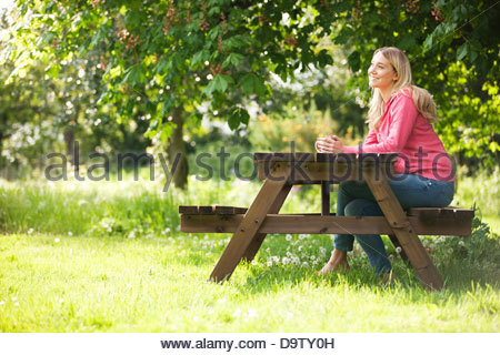 A young woman sitting at a garden bench drinking a hot beverage, smiling - Stock Photo
