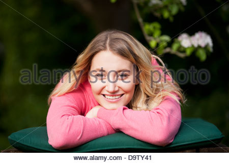 A young woman laying on a sun lounger, smiling - Stock Photo