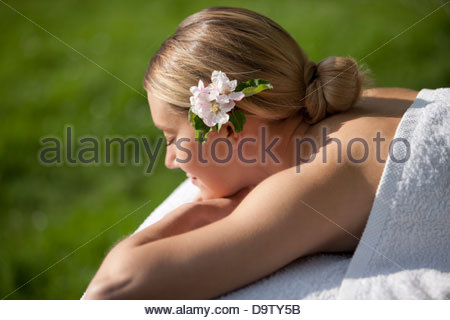 A young woman laying on a massage table with apple blossom in her hair, eyes closed - Stock Photo