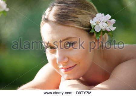 A young woman laying on a massage table with blossom in her hair, close up - Stock Photo