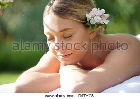 A young woman laying on a massage table with eyes closed, close up - Stock Photo