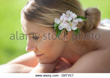 A young woman with blossom in her hair, thinking - Stock Photo