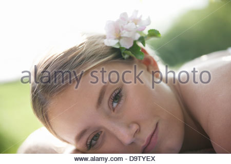 A young woman laying down with apple blossom in her hair - Stock Photo