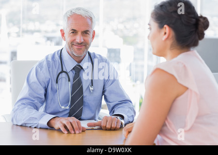 Attractive doctor sitting in front of patient - Stock Photo