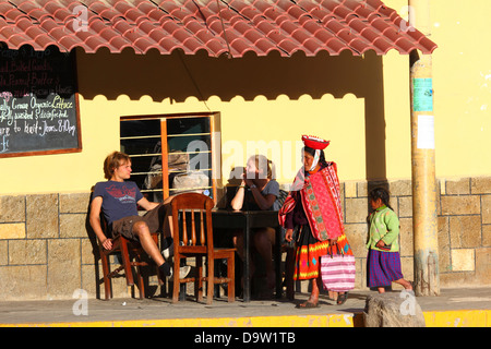 Local indigenous lady walking past tourists sitting at street cafe, Ollantaytambo , Sacred Valley , near Cusco, - Stock Photo