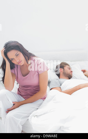 Stressed woman thinking while she is sat in her bed - Stock Photo