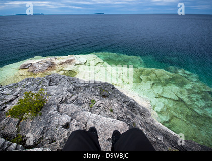 First person view of sitting on a cliff over Georgian Bay at Bruce Peninsula National Park in Ontario, Canada. - Stock Photo