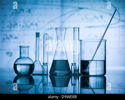 Group of laboratory flasks empty or filled with a clear liquid on blue tint scientific graphics background and their - Stock Photo