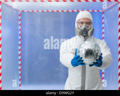 person dressed in a bio hazard protective suit showing a disco ball standing in front of a confinement tent - Stock Photo
