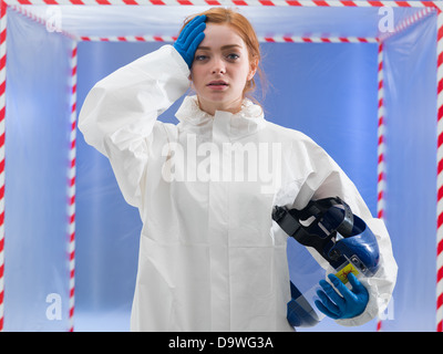 Exhausted or infected female biohazard scientist dressed in a biohazard suit holding her helmet mask in one hand - Stock Photo
