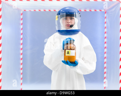 Person in a biohazard suit with a toxic substance in a brown bottle labelled as a poison held in her hands - Stock Photo