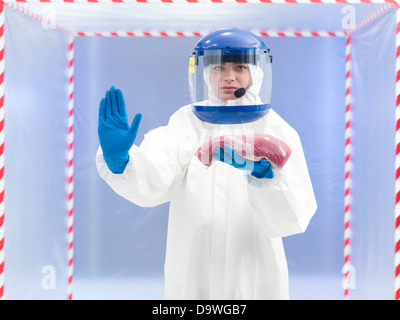 Woman in a biohazard suit with a meat sample in her gloved hand holding up her other hand in a gesture to stop indicating - Stock Photo