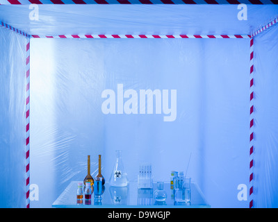 different glass containers filled with differently colored liquids on a glass table in a containment tent, lit by - Stock Photo