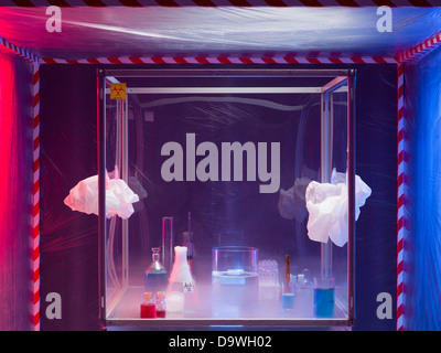 different glass containers filled with differently colored liquids on a glass table in a sterile chamber, in reaction - Stock Photo