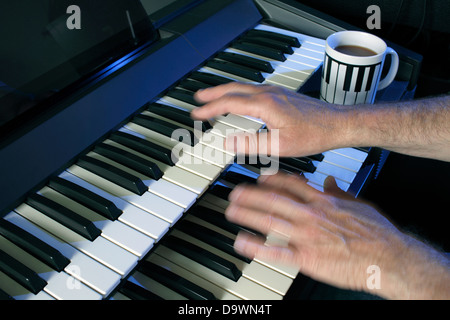 Playing a two manual electric keyboard. - Stock Photo