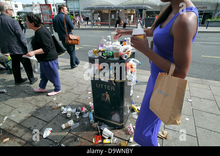 Person placing an empty cup onto an overflowing litter bin. - Stock Photo