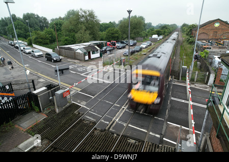 A Birmingham to Leicester train passing over a level crossing at Narborough, Leicestershire. - Stock Photo