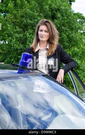 Young female FBI agent standing near car open door - Stock Photo